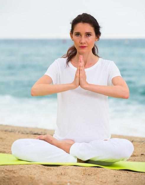 Frau im weißen t-shirt sitzt und übt meditation Kostenlose Fotos