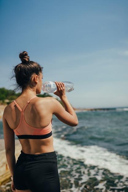 Frau im yoga-outfit, das frisches wasser von der flasche nach übung am strand trinkt Kostenlose Fotos