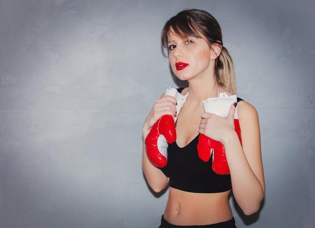 Frau in boxhandschuhen auf grauem hintergrund Premium Fotos