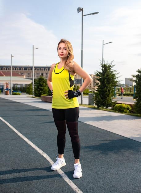 Frau in den gelben und schwarzen sportausstattungen, die auf einer rüttelnden linie stehen und aufwerfen. Kostenlose Fotos