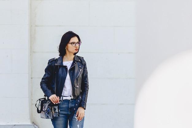 Frau in den gläsern in der lederjacke auf straße Premium Fotos