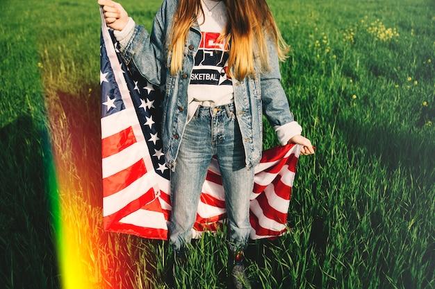 Frau in den jeans, die auf dem gebiet bleiben Kostenlose Fotos
