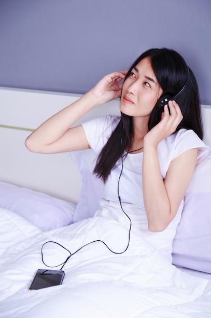 Frau in den kopfhörern, die musik vom smartphone auf bett im schlafzimmer hören Premium Fotos