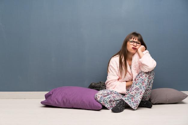Frau in den pyjamas auf dem fußboden störend Premium Fotos