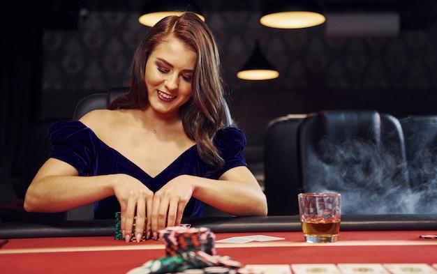 Frau in der eleganten kleidung sitzt im cassino durch tabelle und spielt pokerspiel Premium Fotos