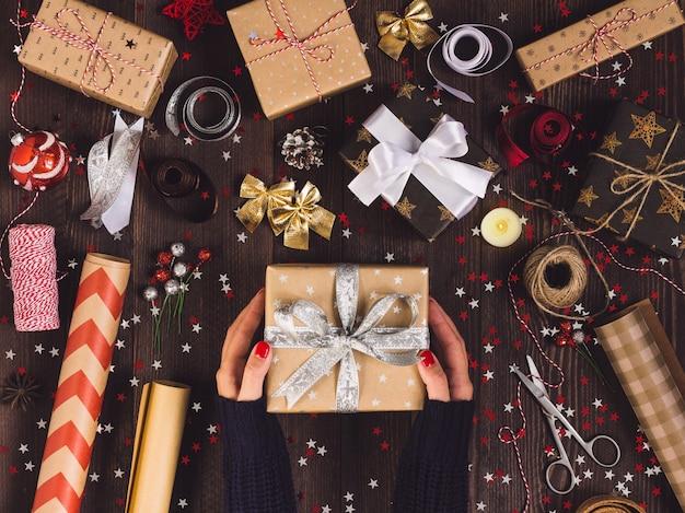 Frau in der hand, die geschenkbox des neuen jahres hält Kostenlose Fotos