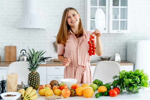 Frau in der küche bereit, mahlzeit mit gemüse und früchten zuzubereiten. Premium Fotos