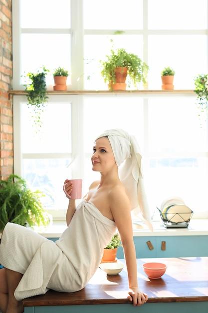 Frau in der küche mit handtuch auf dem kopf nach der dusche Kostenlose Fotos