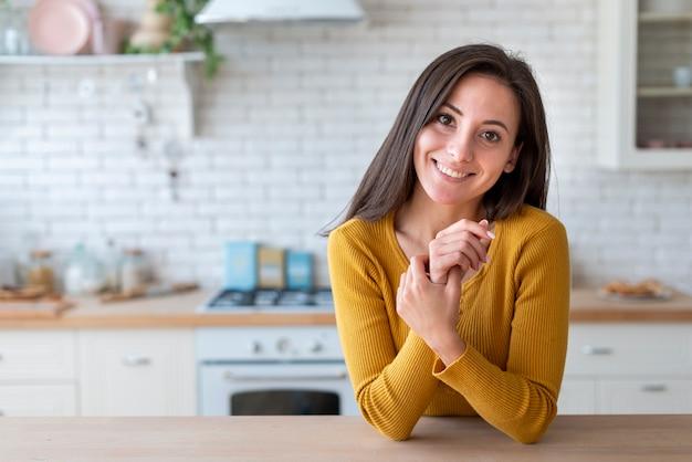 Frau in der küche, welche die kamera betrachtet Kostenlose Fotos