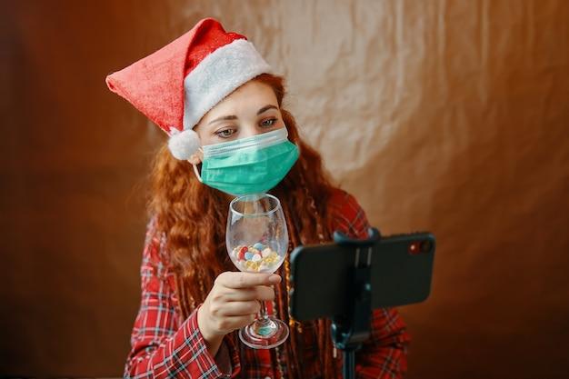 Frau in der medizinischen maske und im weihnachtsmannhut mit glas pillen vor ihrem smartphone. weihnachtsvideoanrufe werden unter quarantäne gestellt. neujahrsstimmung. rothaarige frau mit dreadlocks. Premium Fotos