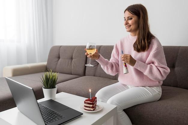 Frau in der quarantäne, die geburtstag mit freunden über laptop und getränk feiert Kostenlose Fotos