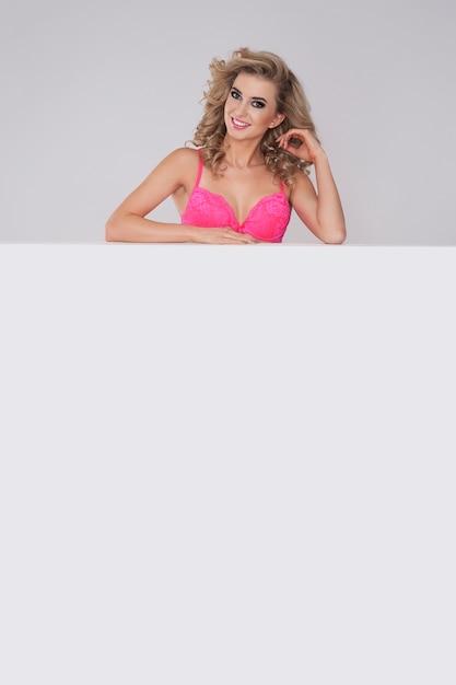 Frau in der rosa unterwäsche, die hinter dem whiteboard steht Kostenlose Fotos