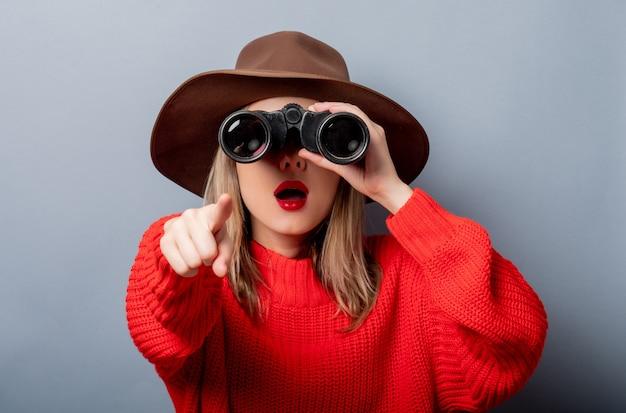 Frau in der roten strickjacke und im hut mit binokularem Premium Fotos