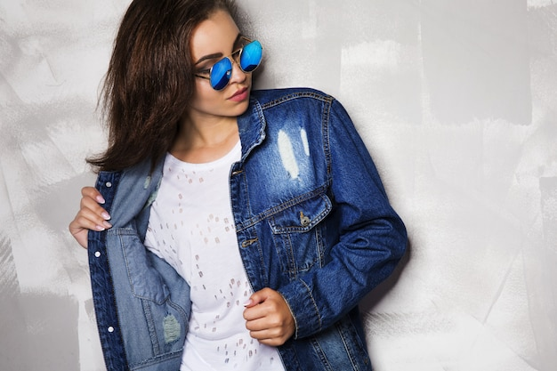 Frau in der runden sonnenbrille, die nahe einer grauen wand aufwirft Premium Fotos