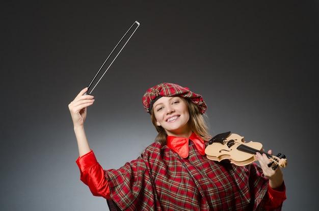 Frau in der schottischen kleidung im musikalischen konzept Premium Fotos