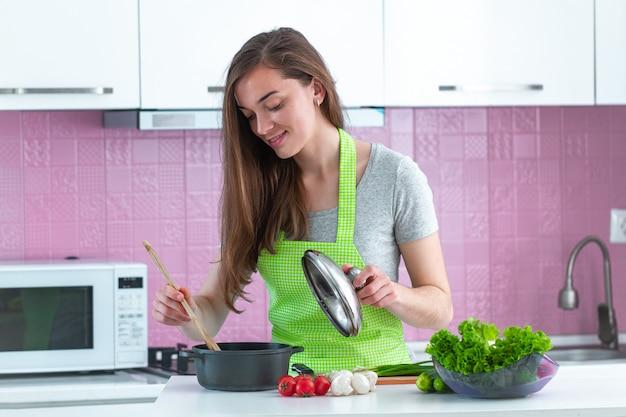 Frau in der schürze, die gerichte aus reifem gemüse für familie zum mittagessen in der küche zu hause kocht. sauberes essen und richtige ernährung. gesunder lebensstil, ernährung Premium Fotos