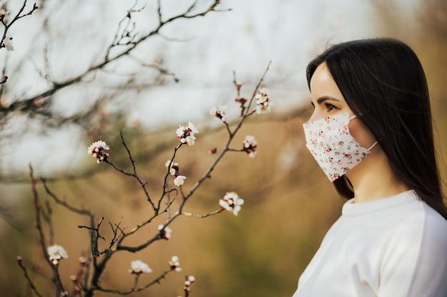Frau in der schützenden medizinischen gesichtsmaske mit blumen nahe blühendem baum im frühjahr. Premium Fotos