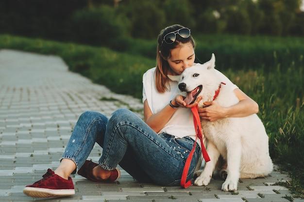 Frau in der sommerkleidung, die auf pflaster mit gekreuzten beinen sitzt, die glücklichen weißen hund mit offenen kiefern, die kamera betrachten, umarmen und küssen Premium Fotos