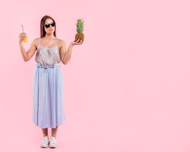 Frau in der sonnenbrille, die glas saft und ananas hält Kostenlose Fotos