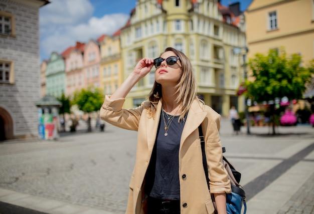Frau in der sonnenbrille und im rucksack in gealtertem stadtzentrumquadrat. polen Premium Fotos