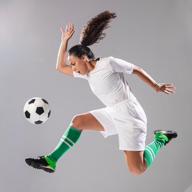 Frau in der sportkleidung, die fußball spielt Kostenlose Fotos