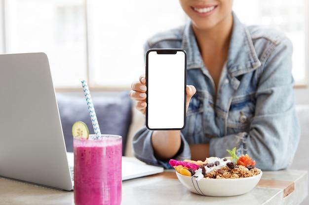 Frau in der stilvollen jeansjacke im kaffeehaus mit leerem smartphonebildschirm Kostenlose Fotos