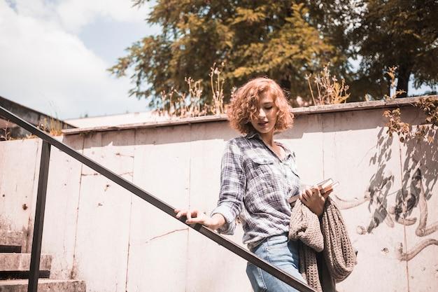 Frau in der straßenabnutzung mit büchern und schal in der hand, die auf schritte hinuntergehen Kostenlose Fotos