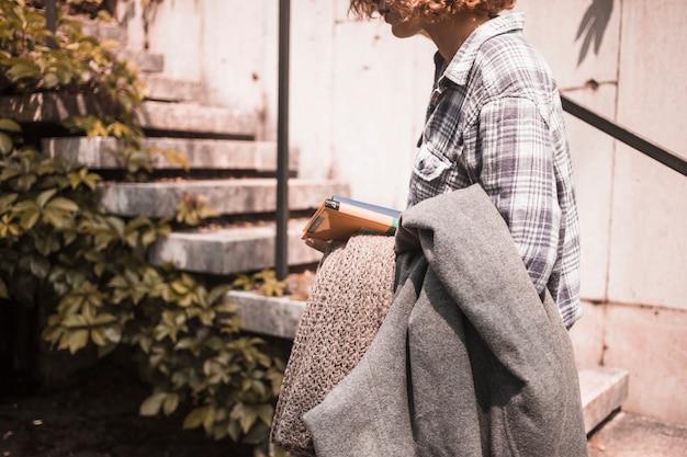 Frau in der straßenabnutzung mit büchern und schal in der hand nahe schritten Kostenlose Fotos