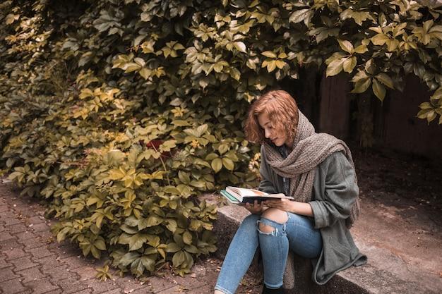 Frau in der straßenbekleidung, die an bord sitzt und lesebuch nahe anlage Kostenlose Fotos