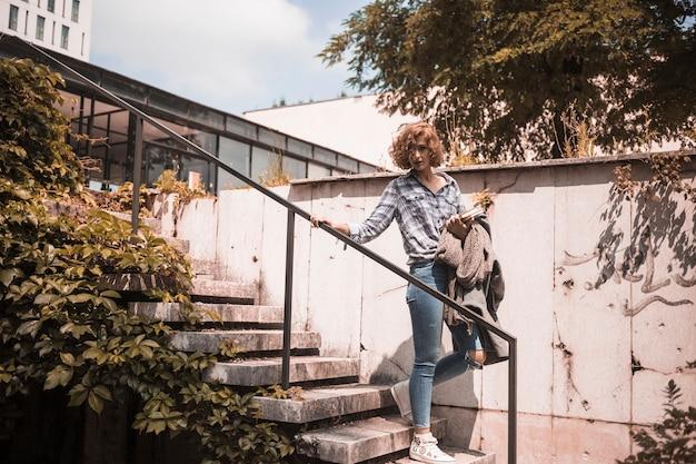 Frau in der straßenbekleidung, die auf schritte hinuntergeht Kostenlose Fotos