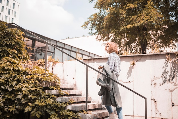 Frau in der straßenbekleidung, die auf schritten steht Kostenlose Fotos