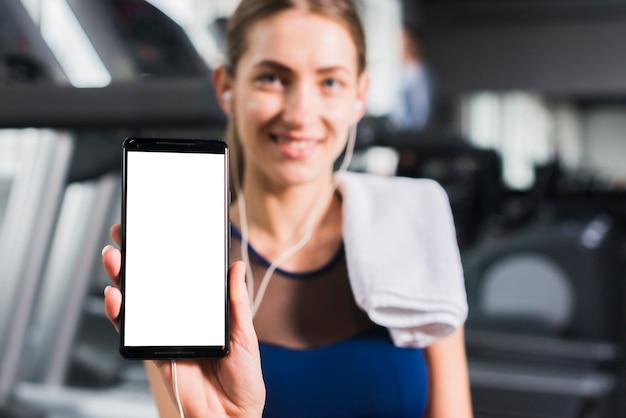 Frau in der turnhalle mit smartphoneschablone Kostenlose Fotos