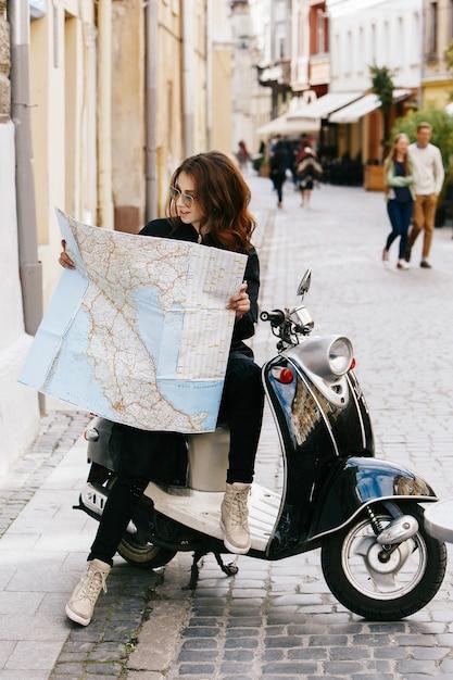 Frau in der ursprünglichen sonnenbrille sitzt auf dem roller mit touristischer karte Kostenlose Fotos