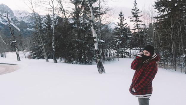 Frau in der warmen jacke auf kiefernhintergrund Kostenlose Fotos