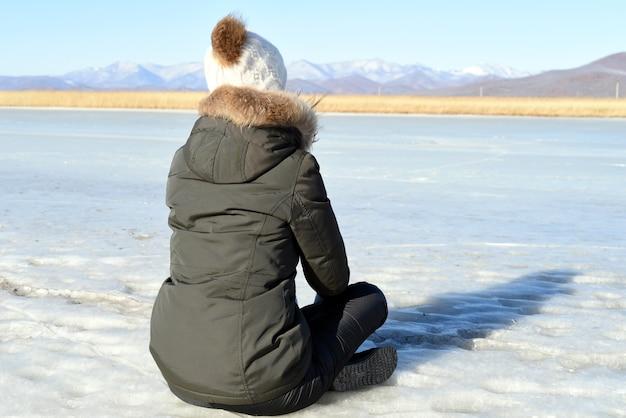Frau in der warmen kleidung, die auf dem eis sitzt und schneebedeckte berge betrachtet Premium Fotos