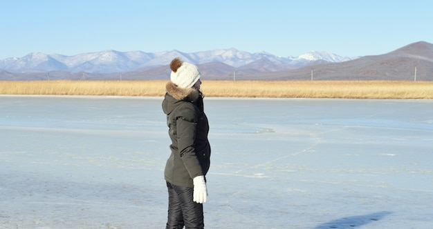 Frau in der warmen kleidung, die auf dem eis steht und wegschaut Premium Fotos
