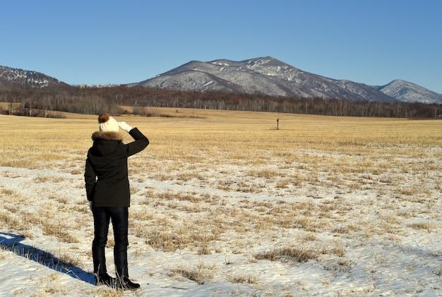Frau in der warmen kleidung, die im feld steht und schneebedeckte berge betrachtet Premium Fotos