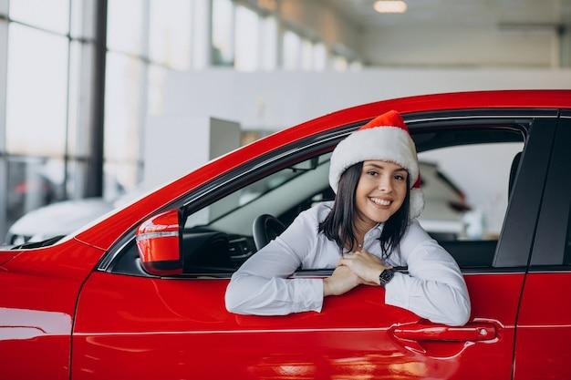 Frau in der weihnachtsmütze durch das rote auto in einem autohaus Kostenlose Fotos