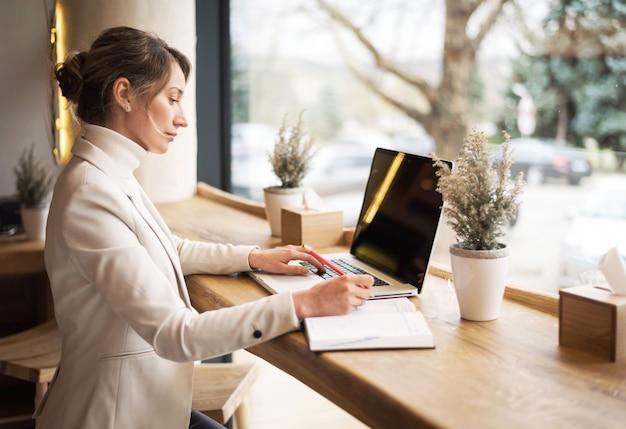 Frau in der weißen reihe, die an laptop am business-lunch arbeitet Premium Fotos