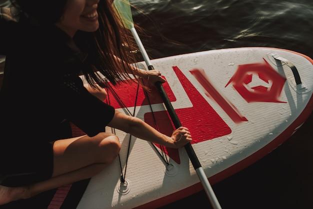 Frau in der wetsuit-rudersport-brandung mit paddel. Premium Fotos