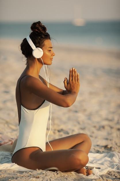 Frau in der yoga-meditations-pose mit kopfhörern am strand Premium Fotos