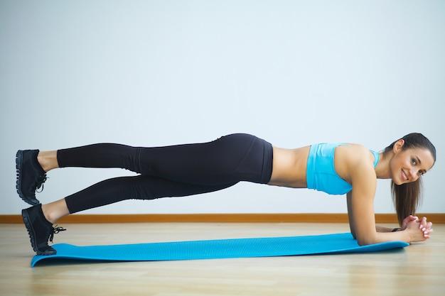Frau in der yogaklasse, die aufwärtsgerichtete hundehaltung macht Premium Fotos