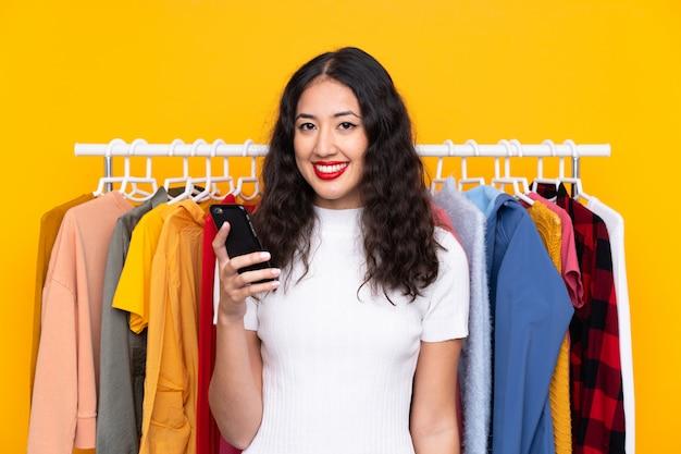 Frau in einem bekleidungsgeschäft und im gespräch mit mobile Premium Fotos