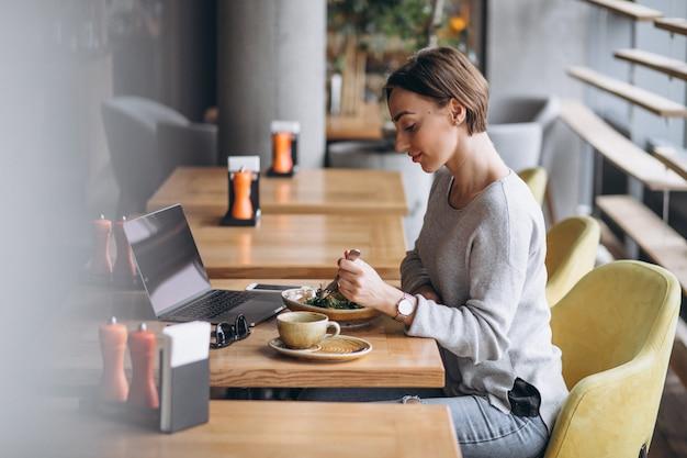 Frau in einem café, das zu mittag isst und am telefon spricht Kostenlose Fotos