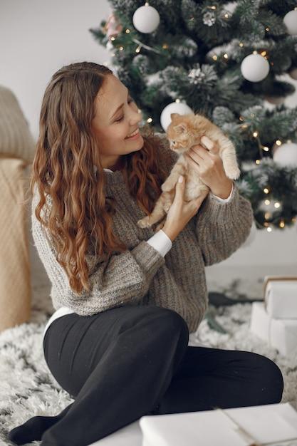 Frau in einem raum. person in einem grauen pullover. dame mit kleiner katze. Kostenlose Fotos