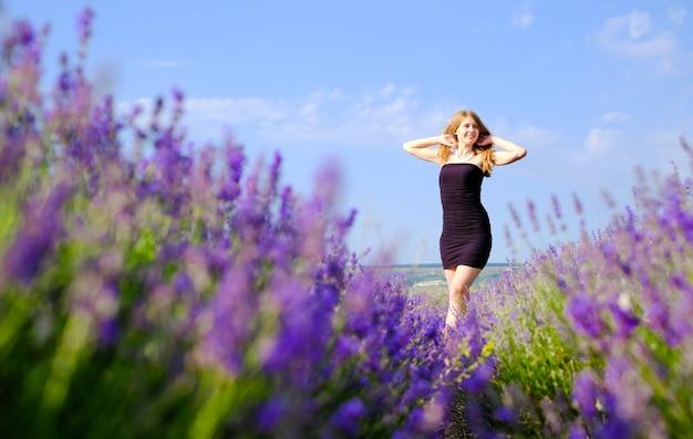 Frau in einem schwarzen kleid, das auf einem blühenden lavendelfeld steht Premium Fotos