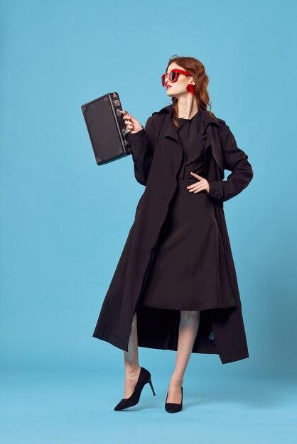 Frau in einem schwarzen umhang mit einem koffer auf einem blauen hintergrund Premium Fotos