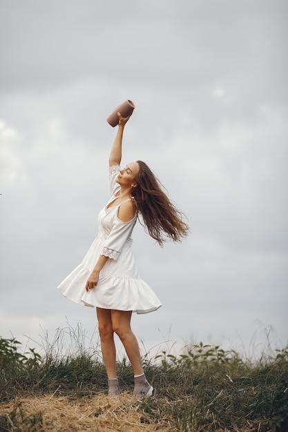Frau in einem sommerfeld. brünette in einem weißen kleid. mädchen mit musiklautsprecher. Kostenlose Fotos