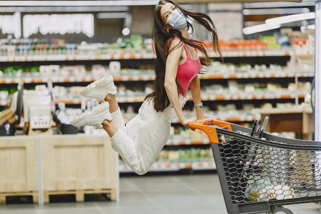 Frau in einem supermarkt. dame in einem beatmungsgerät. mädchen macht parchases. Kostenlose Fotos