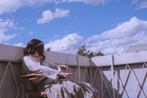 Frau in einem weinlesekleid, das auf dem dach eines gebäudes mit einem schönen blauen himmel und wolken sitzt Kostenlose Fotos
